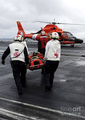 Personnel Carry An Injured Sailor Print by Stocktrek Images