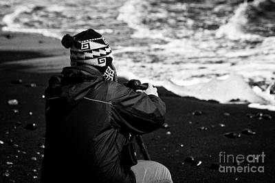 photographer taking photos of Ice washed up on black sand beach at jokulsarlon iceland Print by Joe Fox