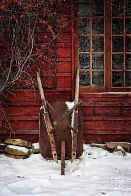 Rusty Wheelbarrow Leaning Against Barn In Winter Print by Sandra Cunningham