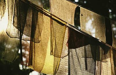 Natural Forces Photograph - Sunlight Filters Through Prayer Flags by Michael Melford