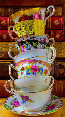 Tea Cups Stacked Against Old Books Print by Garry Gay