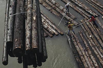 Transportation Of Goods Photograph - Three Men Push Floating Logs by Joel Sartore
