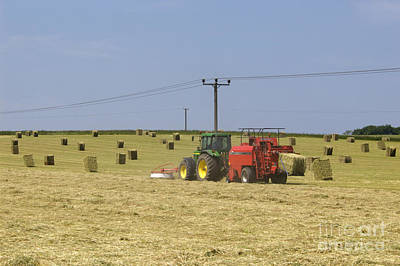 British Photograph - Tractor Bailing Hay In A Field At Harvest Time by Andy Smy