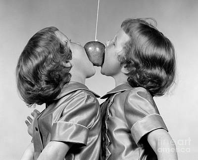 Twin Girls Bobbing For Apple Print by H. Armstrong Roberts/ClassicStock