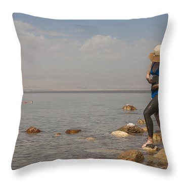 A Woman Smears Therapeutic Dead Sea Mud Throw Pillow by Taylor S. Kennedy
