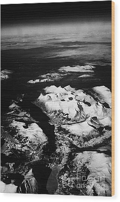 Looking Out Of Aircraft Window Over Snow Covered Fjords And Coastline Of Norway Europe Wood Print by Joe Fox