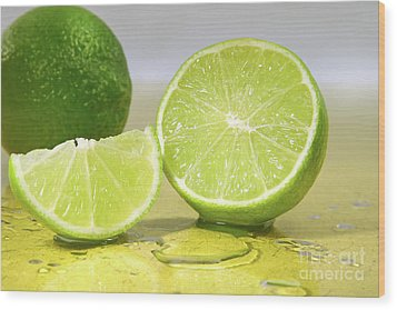 Limes On Yellow Surface Wood Print by Sandra Cunningham
