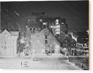 looking out atTromso bryggen quay harbour on a cold snowy winter night troms Norway europe Wood Print by Joe Fox