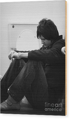 Young Dark Haired Teenage Man Sitting On The Floor Of The Bathroom With Back Against The Wall In The Wood Print by Joe Fox