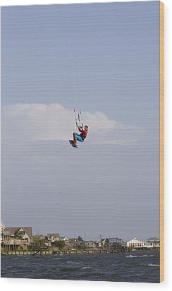 A Kiteboarder Jumps High Over Beach Wood Print by Skip Brown
