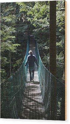 A Man Walks Across A Suspension Bridge Wood Print by Taylor S. Kennedy