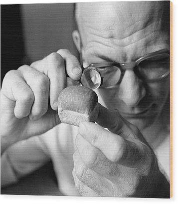 Man Looking At Miniture Loaf Of Bread Through Magnifying Glass Wood Print by Hulton Archive