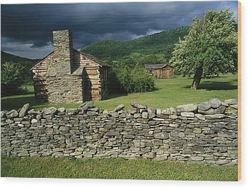 Storm Clouds Form Above Log Buildings Wood Print by Raymond Gehman