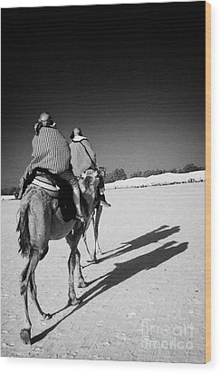two tourists on camels return to base in the sahara desert at Douz Tunisia Wood Print by Joe Fox