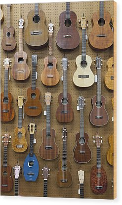 Various Guitars & Ukuleles Hanging From Wall Wood Print by Lisa Romerein