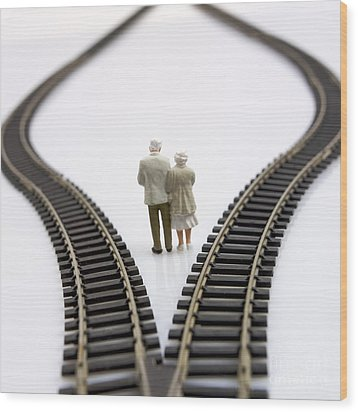 Figurines Between Two Tracks Leading Into Different Directions Symbolic Image For Making Decisions. Wood Print by Bernard Jaubert