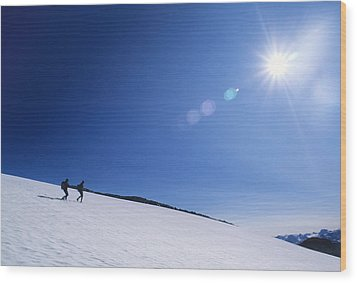 Two Hikers Explore A Snowfield Wood Print by Bill Hatcher