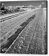 frozen salt and grit covered rural small road in Forget Saskatchewan Canada Acrylic Print by Joe Fox