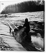 man on snowmobile crossing frozen fields in rural Forget canada Acrylic Print by Joe Fox
