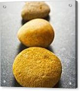 Straight Line Of Brown Pebbles On Dark Background Acrylic Print by Colin and Linda McKie