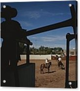 A Silhouetted Cowboy Watches Riders Acrylic Print by Raul Touzon