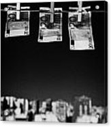 Three Twenty Euro Banknotes Hanging On A Washing Line With Blue Sky Over City Skyline Acrylic Print by Joe Fox