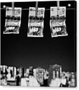 Three Twenty Pounds Sterling Banknotes Hanging On A Washing Line With Blue Sky Above A City Skyline Acrylic Print by Joe Fox