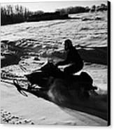 man on snowmobile crossing frozen fields in rural Forget Saskatchewan Canvas Print by Joe Fox