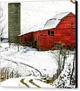 Red Barn In Snow Canvas Print by John Haldane