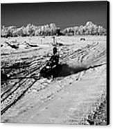two men on snowmobiles crossing frozen fields in rural Forget Saskatchewan Canada Canvas Print by Joe Fox