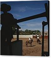 A Silhouetted Cowboy Watches Riders Canvas Print by Raul Touzon