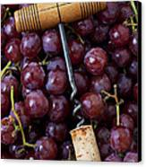 Corkscrew And Wine Cork On Red Grapes Canvas Print by Garry Gay