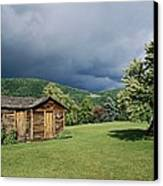 Storm Clouds Form Above A Log Cabin Canvas Print by Raymond Gehman