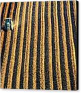Tractor Plowing A Field Canvas Print by John Short
