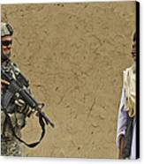 U.s. Army Specialist Talks To An Afghan Canvas Print by Stocktrek Images
