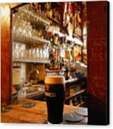 A Pint Of Dark Beer Sits In A Pub Canvas Print by Jim Richardson