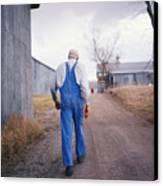 An Elderly Farmer In Overalls Walks Canvas Print by Joel Sartore