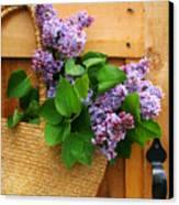 Lilacs In A Straw Purse Canvas Print by Sandra Cunningham