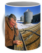 A Farmer Runs His Corn Through His Hand Coffee Mug by Joel Sartore