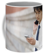A Young Businessman Checks His Text Coffee Mug by Justin Guariglia