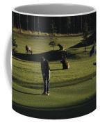 Two People Play Golf While Elk Graze Coffee Mug by Raymond Gehman