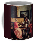A Man And A Woman Seated By A Virginal Coffee Mug by Gabriel Metsu