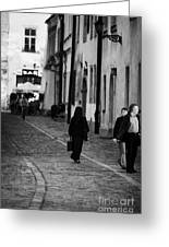 nun with briefcase walking up cobblestone street Kanonicza past tourists in old town krakow Greeting Card by Joe Fox