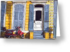 Red Scooter With Yellow House And Blue Shutters Greeting Card by John Boles