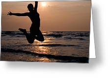 Silhouette Of A Girl Jumping In The Ocean At Sunset Greeting Card by William Langeveld