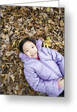 Smiling Girl Lying On Autumn Leaves Greeting Card by Ian Boddy