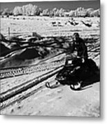 man on snowmobile crossing frozen fields in rural Forget Saskatchewan Canada Metal Print by Joe Fox