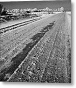 frozen salt and grit covered rural small road in Forget Saskatchewan Canada Metal Print by Joe Fox