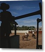 A Silhouetted Cowboy Watches Riders Metal Print by Raul Touzon