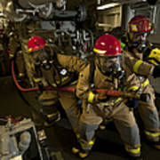 Firemen Combat A Simulated Fire Aboard Poster by Stocktrek Images